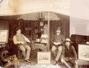 "The Treasury tent of Buffalo Bill's world-famous Wild West Show, probably around 1900.  The photo shows (left to right) Jule Keen, the show's treasurer; William McCune, a former Army colonel; and Jim Mitchell, a ""pretty tough"" cowboy who rode bucking broncos. Behind Mitchell is a safe with a throw over it. You can see the combination lock for the safe.  (Photo courtesy Buffalo Bill Museum and Grave0"