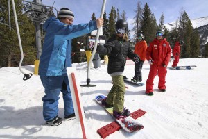 Instructors get a young snowboarder pointed in the right direction.