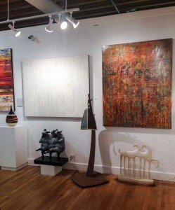 "Abstract acrylic paintings by Hilario Gutierrez have been a popular new addition to the gallery. The three shown above are, left to right, ""When You Come This Way,"" ""Suddenly Quiet"" and ""Jewel at My Feet."" On the floor, the three little sheep are by Giuseppe Palumbo and the horses are by Linda Raynolds."