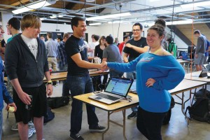 Jose Vietez, co-founder and co-director of Boomtown, shakes hands with up-and-coming programmer Brittany Ann Kos at April's Hack CU.