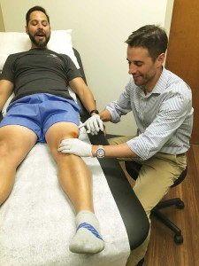 Dr. Jason Glowney, right, works with a patient at CU's Sports Medicine and  Performance Center. (photo courtesy Jason Glowney)